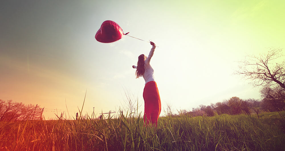 Girl in field holding a heart balloon